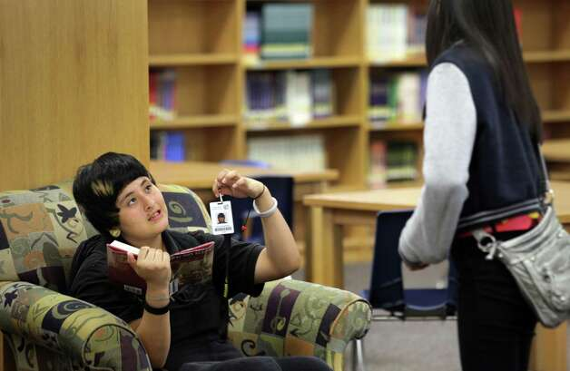 Kayla Saucedo, left, shows her ID badge to a fellow student.  Students at Anson Jones Middle School are using new identification badges that have a built in chip that enables school attendance workers to see where a student is while on campus.  Oct. 1, 2012. Photo: BOB OWEN, San Antonio Express-News / © 2012 San Antonio Express-News