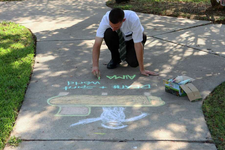 Mormon missionaries Elder Caden Jensen draws sidewalk art in the Clear Lake area as part of mission work Tuesday, Sept. 18, 2012, in Houston.  The missionaries produce artwork on sidewalks in parks and neighborhoods and public areas hoping people will inquire and give them an opportunity to talk about the LDS church. ( James Nielsen / Chronicle ) Photo: James Nielsen / © Houston Chronicle 2012