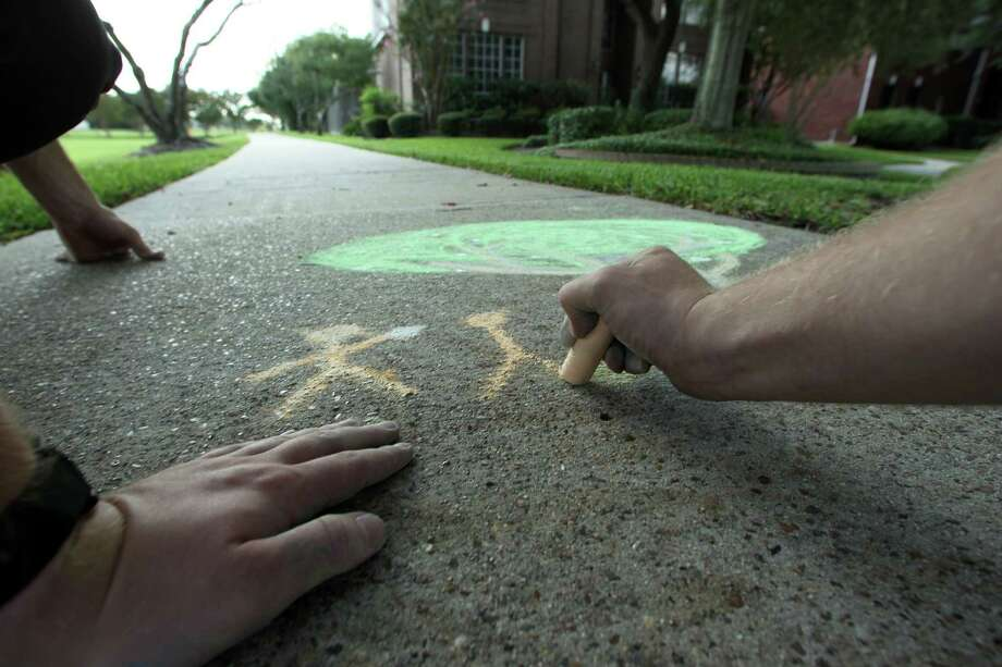 Mormon missionaries draw chalk stick figures and a tree outside of a Clear Lake area home Photo: James Nielsen / © Houston Chronicle 2012