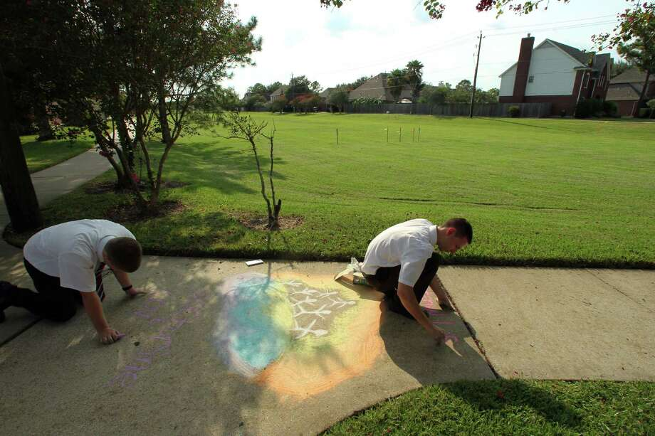 Mormon missionaries Elder Ryan MacCarthy top, and Elder Caden Jensen use bright chalk colors to communicate LDS beliefs. Photo: James Nielsen / © Houston Chronicle 2012
