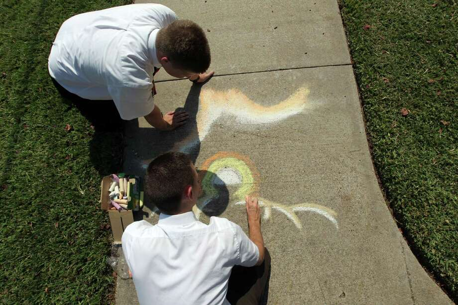 Mormon missionaries Elder Ryan MacCarthy top, and Elder Caden Jensen start to draw pre-Earth from scripture Abraham 3:22 Photo: James Nielsen / © Houston Chronicle 2012