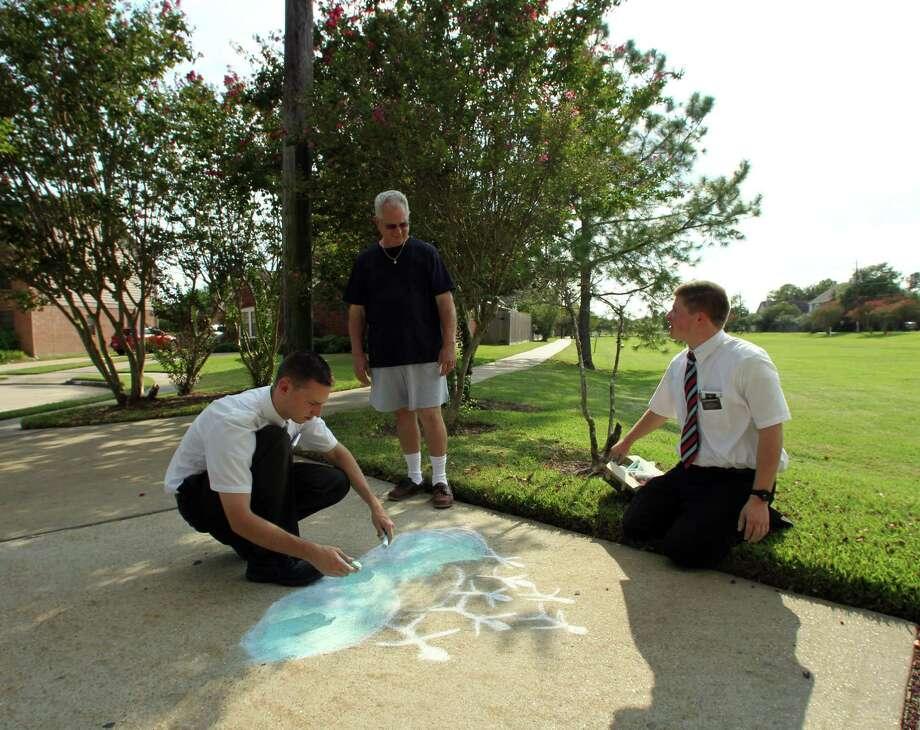 Resident George Childress center, looks on as Mormon missionaries Elder Caden Jensen left, and Elder Ryan MacCarthy draw sidewalk art.  Photo: James Nielsen / © Houston Chronicle 2012