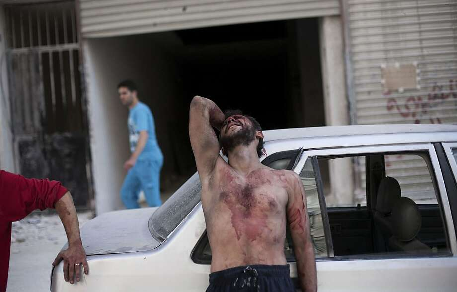 A Syrian man cries outside the Dar El Shifa hospital in Aleppo, Syria after his daughter was injured during a Syrian Air Force strike over a school where hundreds of refugees had taken shelter Thursday, Oct. 4, 2012. The border violence between Turkey and Syria has added a dangerous new dimension to Syria's civil war, dragging Syria's neighbors deeper into a conflict that activists say has already killed 30,000 people since an uprising against President Bashar Assad's regime began in March 2011. (AP Photo/ Manu Brabo) Photo: Manu Brabo, Associated Press