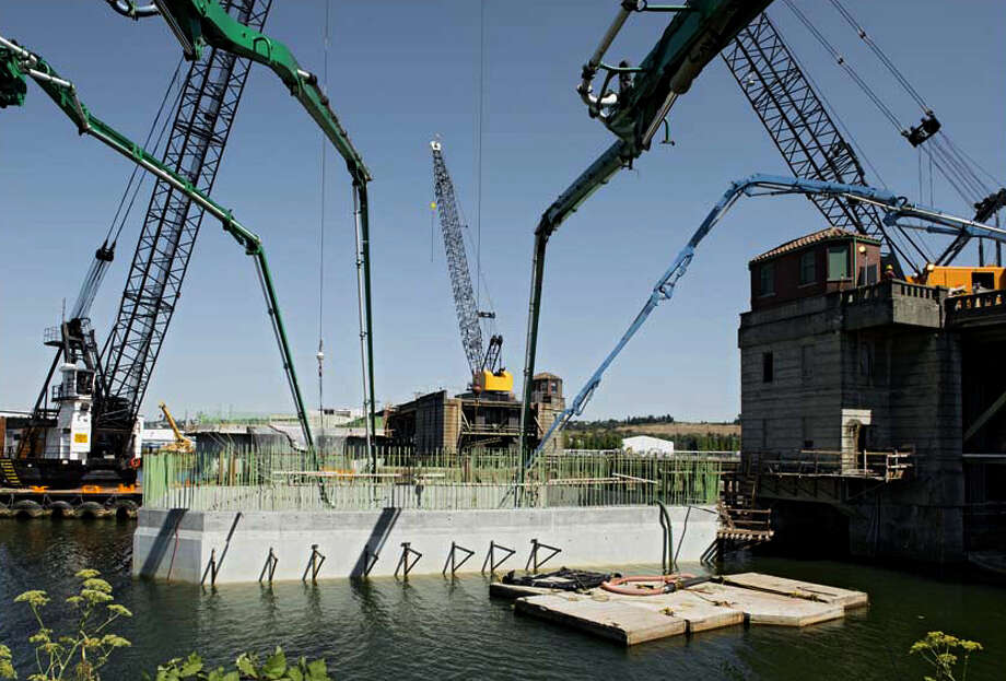 Crews pump concrete into one of the new bridge's main piers. About 2,500 cubic yards of concrete is used to form the giant plug in each of the main piers, which is enough to fill 250 trucks.  Photo: John Stamets / 2012