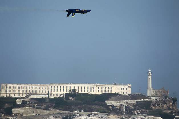 A Blue Angels F/A 18 jet flies inverted past Alcatraz during a practice session for Saturday's performance in San Francisco, Calif. on Thursday, Oct. 4, 2012. Photo: Paul Chinn, The Chronicle