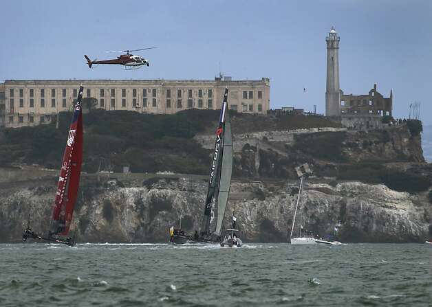 A helicopter hovers above Emirates Team New Zealand and Energy Team of France as the catamarans race towards Alcatraz in a quarterfinals match of the America's Cup World Series in San Francisco, Calif. on Thursday, Oct. 4, 2012. Photo: Paul Chinn, The Chronicle