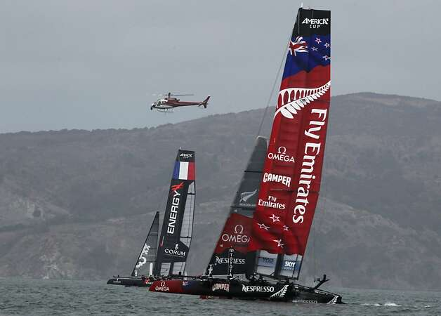 A helicopter hovers above Energy Team of France and Emirates Team New Zealand as the catamarans race in a quarterfinals match of the America's Cup World Series in San Francisco, Calif. on Thursday, Oct. 4, 2012. Photo: Paul Chinn, The Chronicle