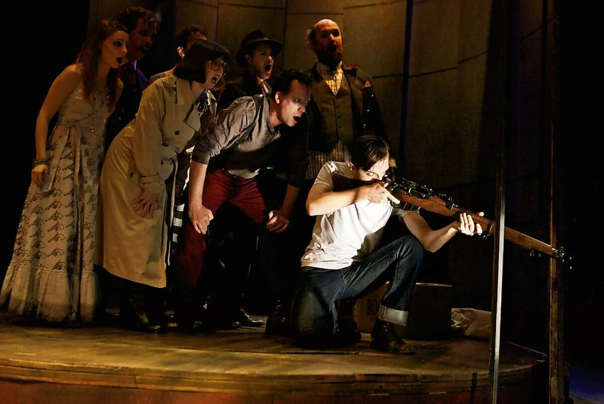Lee Harvey Oswald (Kevin Singer, right) takes aim, urged on by a chorus of presidential assassins in Shotgun Players' production of the Stephen Sondheim musical