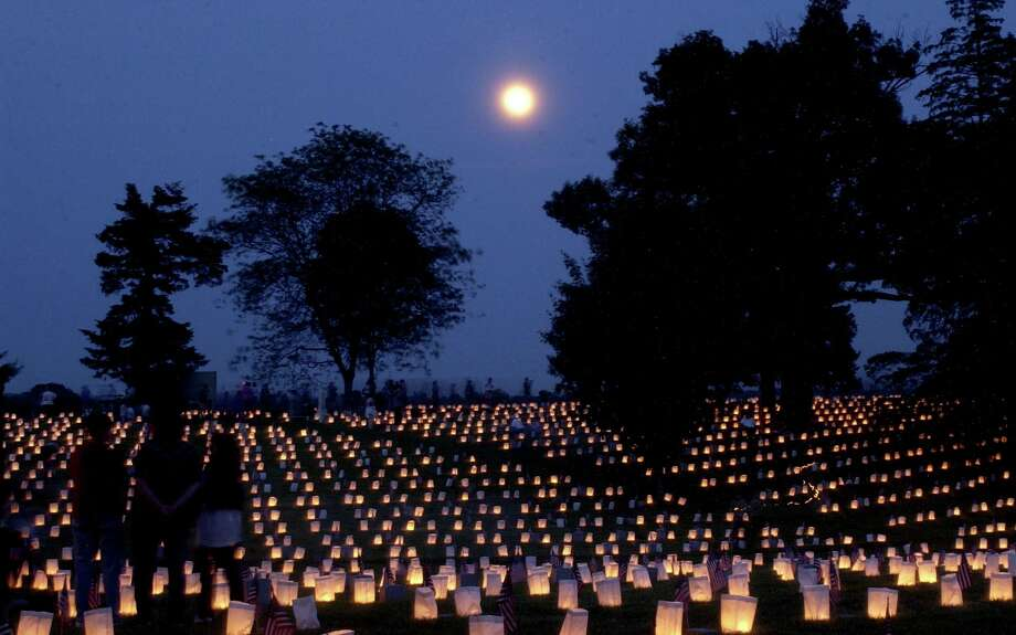 "As a full moon rises over Fredericksburg, Va., 15,000 candles light the gravesites of Union Soldiers at the National Cemetery. The tradition called Lumineria, which started in 1997, is the highlight of ""Lest We Forget: Fredericksburg Civil War Weekend,"" and draws thousands of visitors to the site. Photo: REZA A MARVASHTI / THE FREE LANCE-STAR"