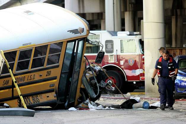 Emergency responders clean up after a collision caused a San Antonio ISD school bus to crash through a guardrail and fall off I-37 near Houston Street.  A 7-year-old student and two San Antonio Independent School District staffers were injured. Photo: Helen L. Montoya, San Antonio Express-News / ©SAN ANTONIO EXPRESS-NEWS
