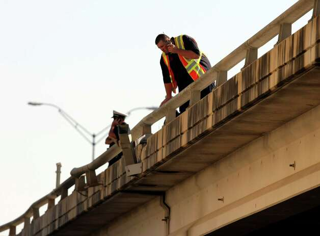 San Antonio Police officers stand on I-37 near Houston viewing the scene after a collision caused a San Antonio ISD school bus to crash through a guardrail and fall off I-37 near Houston Street.  A 7-year-old student and two San Antonio Independent School District staffers were injured. Photo: Helen L. Montoya, San Antonio Express-News / ©SAN ANTONIO EXPRESS-NEWS
