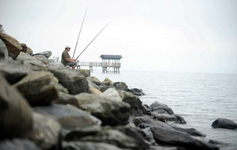 Bryan Golembowski, of Bethany, fishes off the rocks at Gulf Beach in Milford, Thursday, Oct. 4, 2012. Photo: Autumn Driscoll / Connecticut Post