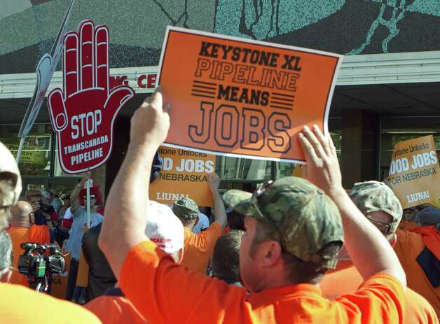 In this Sept. 11, 2011, file photo demonstrators for and against the Keystone XL pipeline gather near the state Capitol in Lincoln, Neb., as public hearings take place about the proposed Keystone XL Pipeline, which would carry tar sands oil from Canada to Texas through the sandhills of Nebraska. Supporters of the pipeline, which include labor unions and business groups, spoke of jobs and development and energy security. AFL-CIO leaders hope to smooth tensions at their executive council's annual winter meeting that starts Monday, March 12, 2012, in Orlando, Fla., with union leaders trying to repair bitter divisions over Obama's rejection of the pipelines. (AP Photo/Nati Harnik, File) Photo: AP, STF / AP