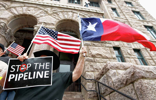 Eddy Radillo of Yantis, sings and holds a Texas flag and a sign opposing the Transcanada Keystone Pipeline in this, Feb. 17, 2012 file photo taken outside of the Lamar County Courthouse in Paris, Texas. Texas landowners are vowing to fight on despite a Lamar County judge's ruling that TransCanada can run a pipeline across private property to bring crude oil to Gulf Coast refineries. (AP Photo/The Paris News, Sam Craft, File) MANDATORY CREDIT Photo: AP, MBR / The Paris News