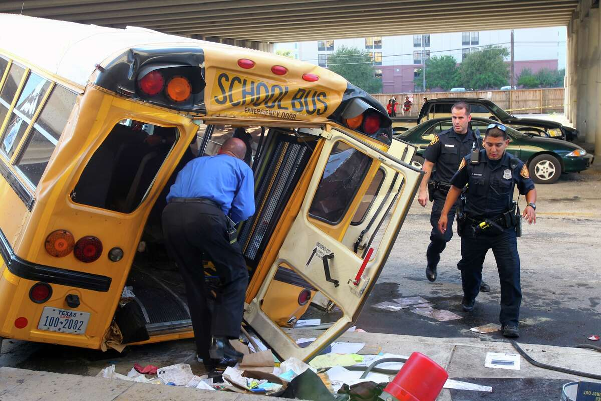Emergency responders clean up after a collision caused a San Antonio ISD school bus to crash through a guardrail and fall off an elevated portion of I-37 near Houston Street in Downtown San Antonio. A 7-year-old student and two San Antonio Independent School District staffers were injured.