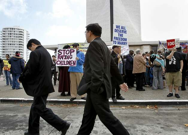 Priests attending the ceremony walk past protesters on Geary Boulevard. Photo: Brant Ward, The Chronicle