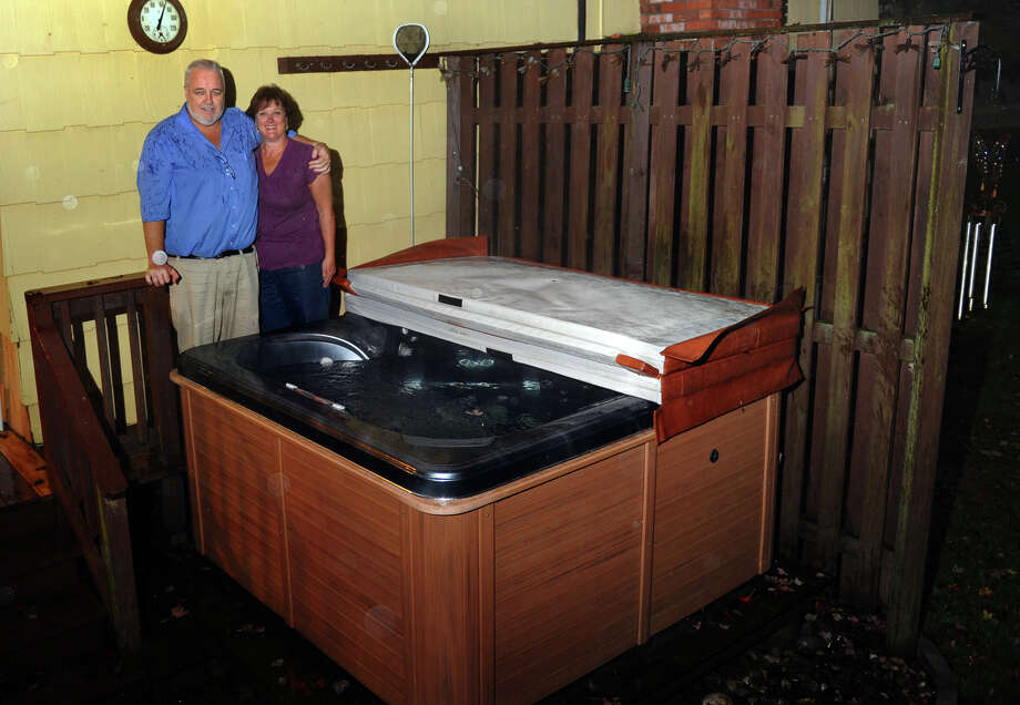 John and Anna Henry pose with the troublesome hot tub they purchased at their home in Trumbull, Conn. on Thursday October 4, 2012. Photo: Christian Abraham / Connecticut Post