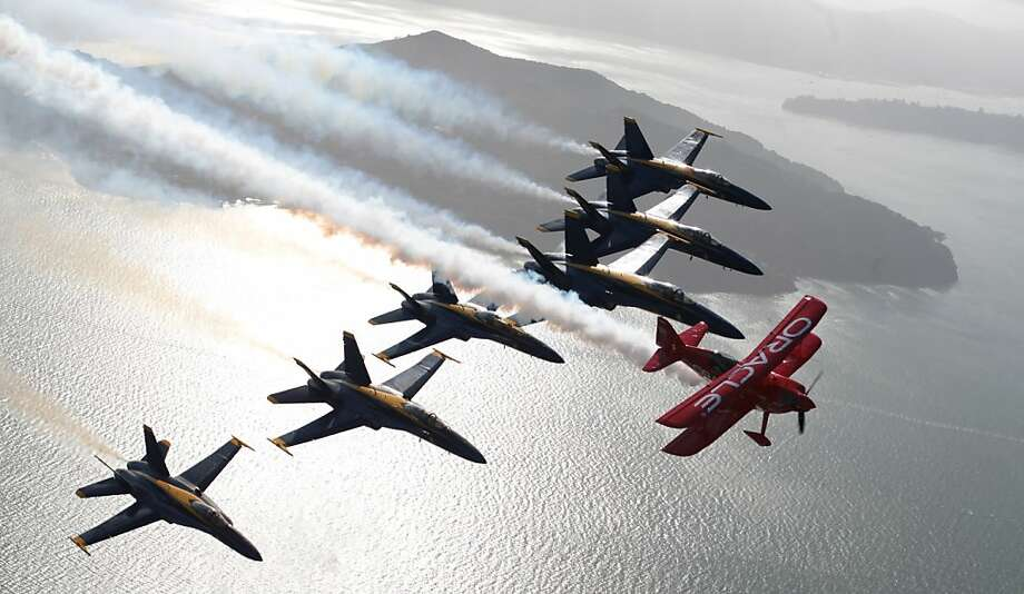 The Blue Angels provide an imposing cover for stunt pilot Sean D. Tucker over San Francisco Bay. Photo: Mathew Sumner, Special To The Chronicle