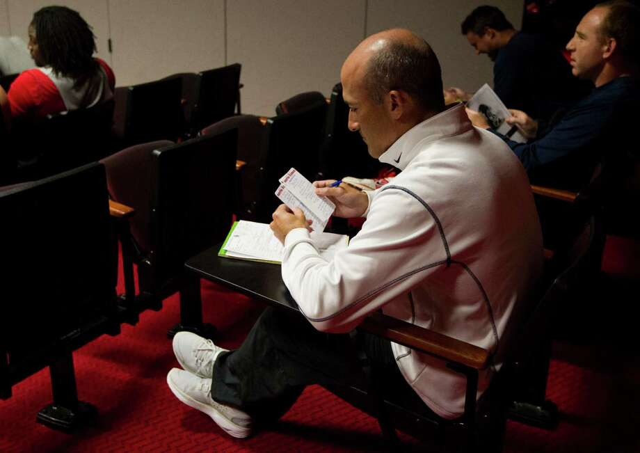 University of Houston head football coach Tony Levine reads his things to do list as he sits in the back of the auditorium during a special teams meeting during the early afternoon. Photo: J. Patric Schneider, For The Chronicle / © 2012 Houston Chronicle