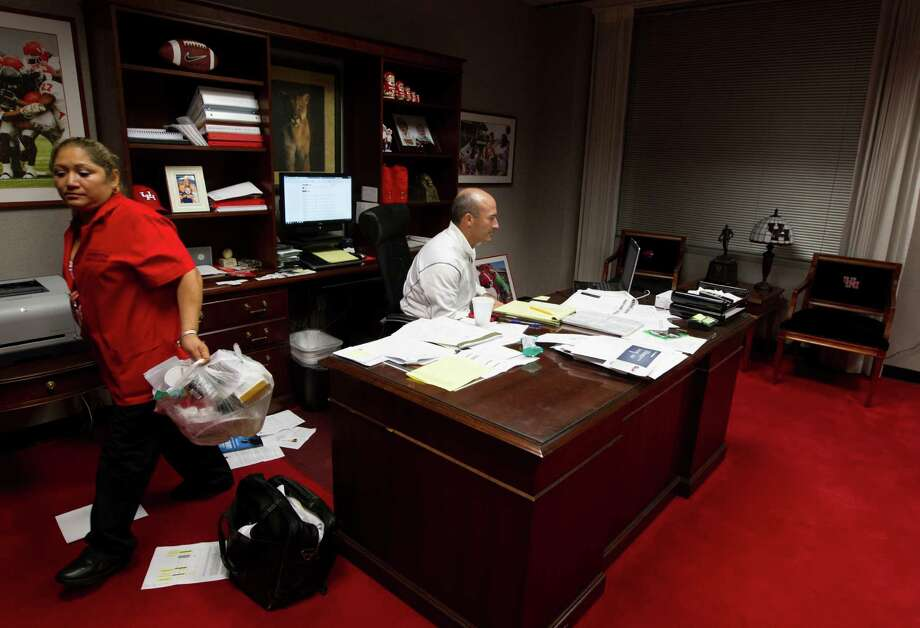 Custodial worker Miriam Gomez goes about her business as UH  football coach Tony Levine works late into the evening in his  office. Photo: J. Patric Schneider, For The Chronicle / © 2012 Houston Chronicle