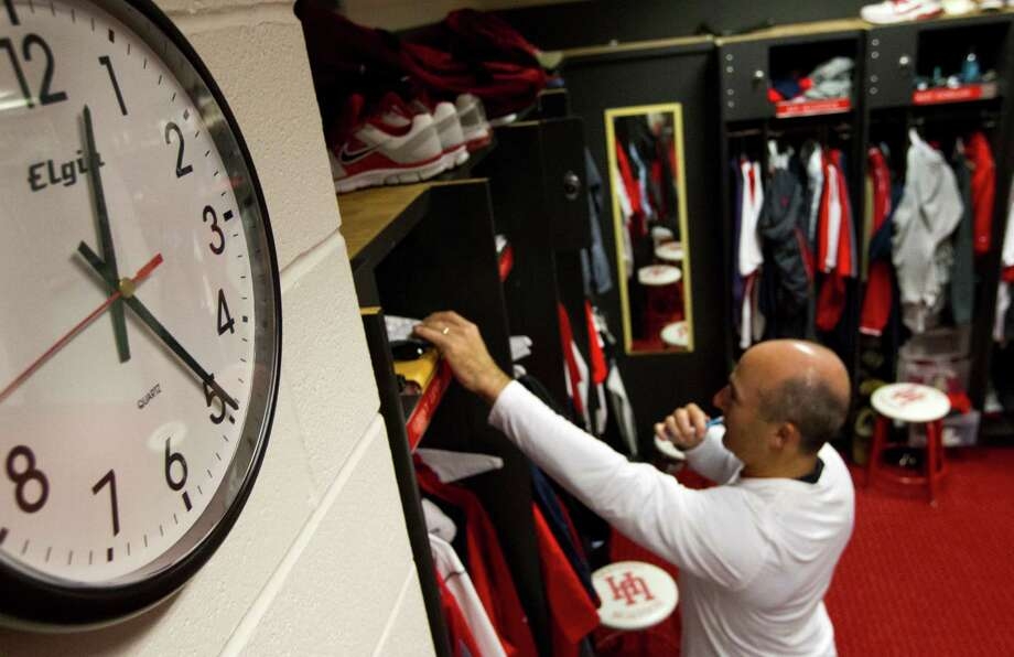University of Houston head football coach Tony Levine brushes his teeth as he prepares for bed. Due to the long hours, Levine often spends the night during the week in his office. Photo: J. Patric Schneider, For The Chronicle / © 2012 Houston Chronicle