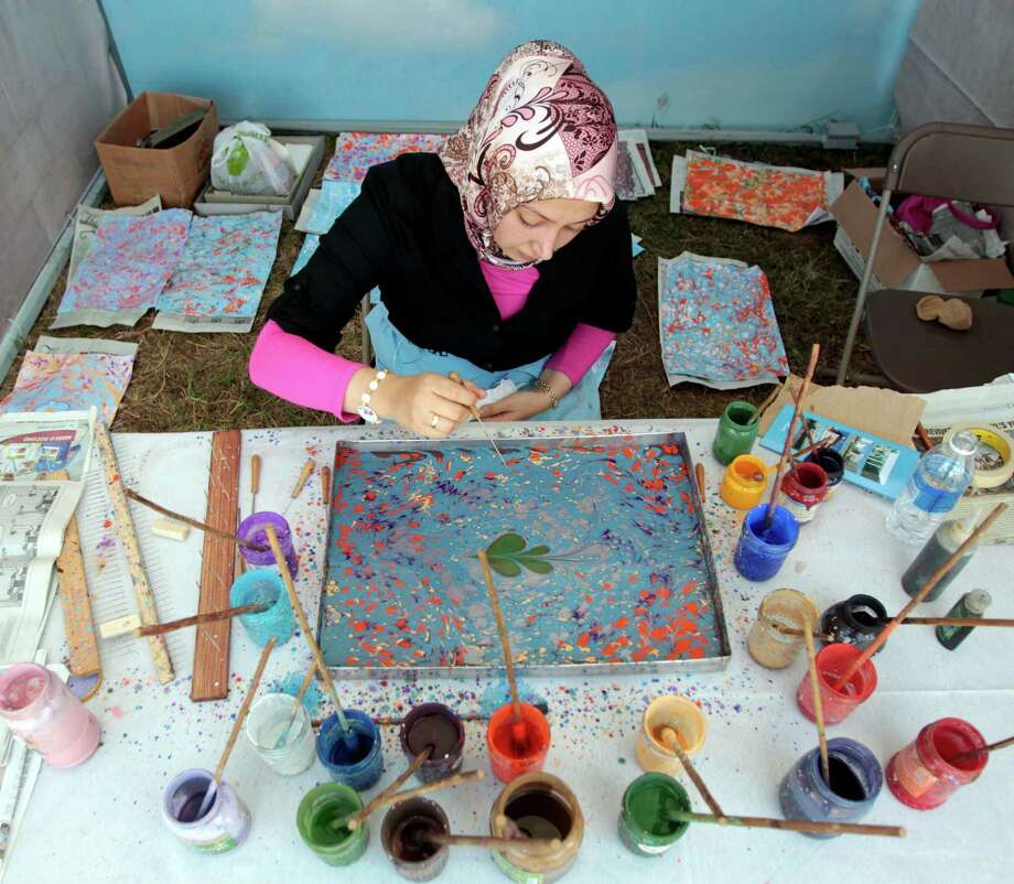 "Ayse Baskoc creates marbled paper, called ""Ebru"" at the Silk Road Festival Thursday. Photo: Billy Smith II, Chronicle / © 2012 Houston Chronicle"