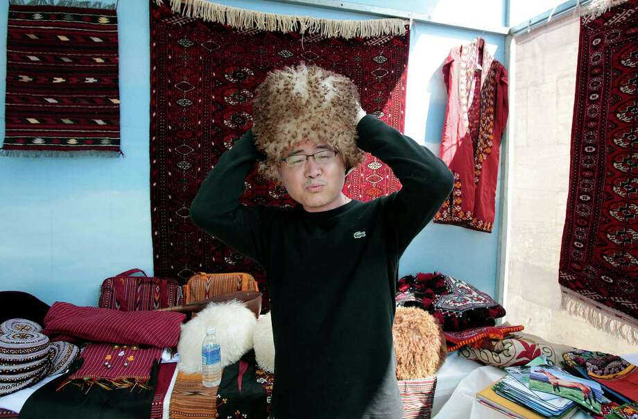 "Houstonian Joseph Nguyen dons a ""telpek,""  a traditional Turkmenistan hat at the Silk Road Festival on Thursday. Photo: Billy Smith II, Chronicle / © 2012 Houston Chronicle"
