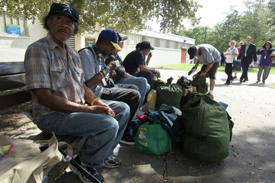 Army veteran Cliff Gardner, left, sits on a bench with other veterans during the 12th annual Stand Down for Homeless Veterans at Emancipation Park on Thursday. Photo: James Nielsen, Chronicle / © Houston Chronicle 2012