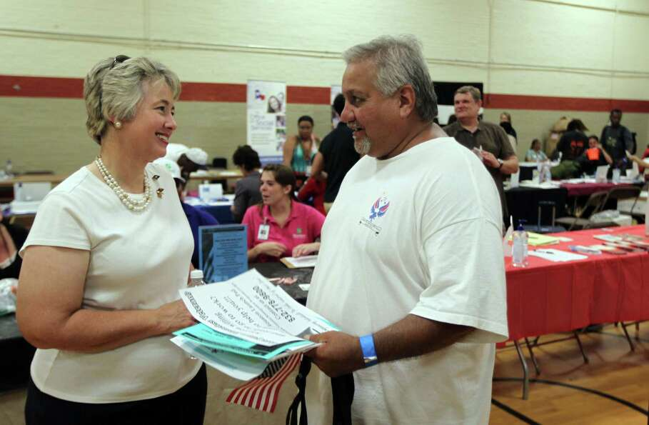 Houston Mayor Annise Parker, left, speaks with Marine veteran Anthony Heysquierdo during the 12th an