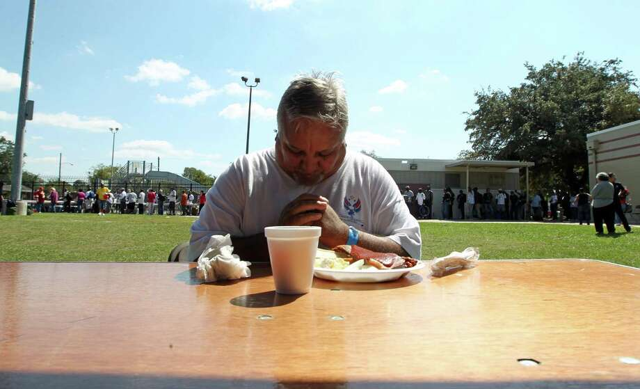 Marine veteran Anthony Heysquierdo prays before eating lunch during Thursday's Stand Down for Homeless Veterans. Photo: James Nielsen, Chronicle / © Houston Chronicle 2012