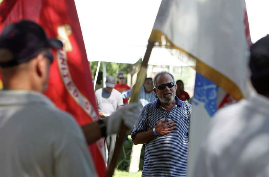 Navy veteran William Collin, center, stands during the national anthem at Thursday's proceedings at the Emancipation Park Community Center. Photo: James Nielsen, Chronicle / © Houston Chronicle 2012