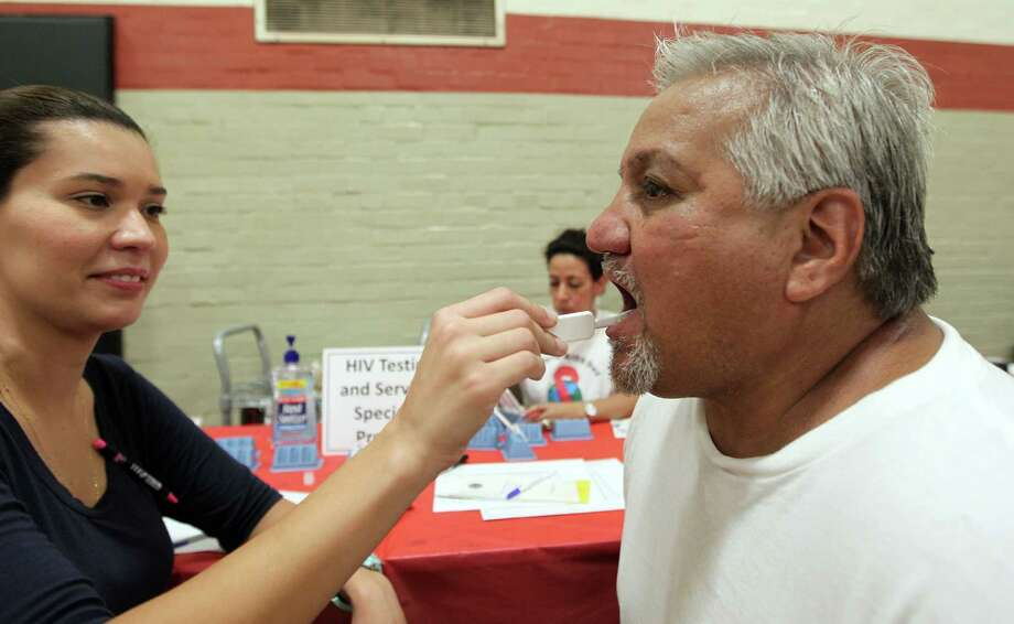 VA medical center's Brenda Clark, left, wipes a swag in Marine veteran Anthony Heysquierdo's mouth during a HIV test at the 12th annual Stand Down for Homeless Veterans at Emancipation Park on Thursday. Photo: James Nielsen, Chronicle / © Houston Chronicle 2012