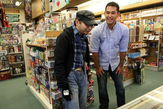 Guido Abenes (left), a 25-year-old who is autistic, checks out cards at a game store in Berkeley with his social mentor, Ben Nomura-Weingrow. Photo: Liz Hafalia, The Chronicle / SF
