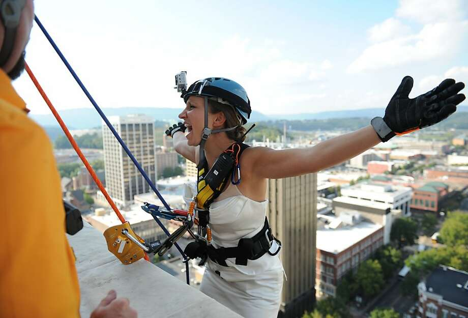 Bride-to-be Meredith Lewallen lets go of her harness right before she rappels down the side of the SunTrust building as part Over the Edge, a RiverRocks festival kickoff event, Thursday, Oct. 4, 2012. Lewallen will be married on Saturday and wanted to commemorate her wedding with a rappel. (AP Photo/Chattanooga Times Free Press, Allison Love) Photo: Allison Love, Associated Press