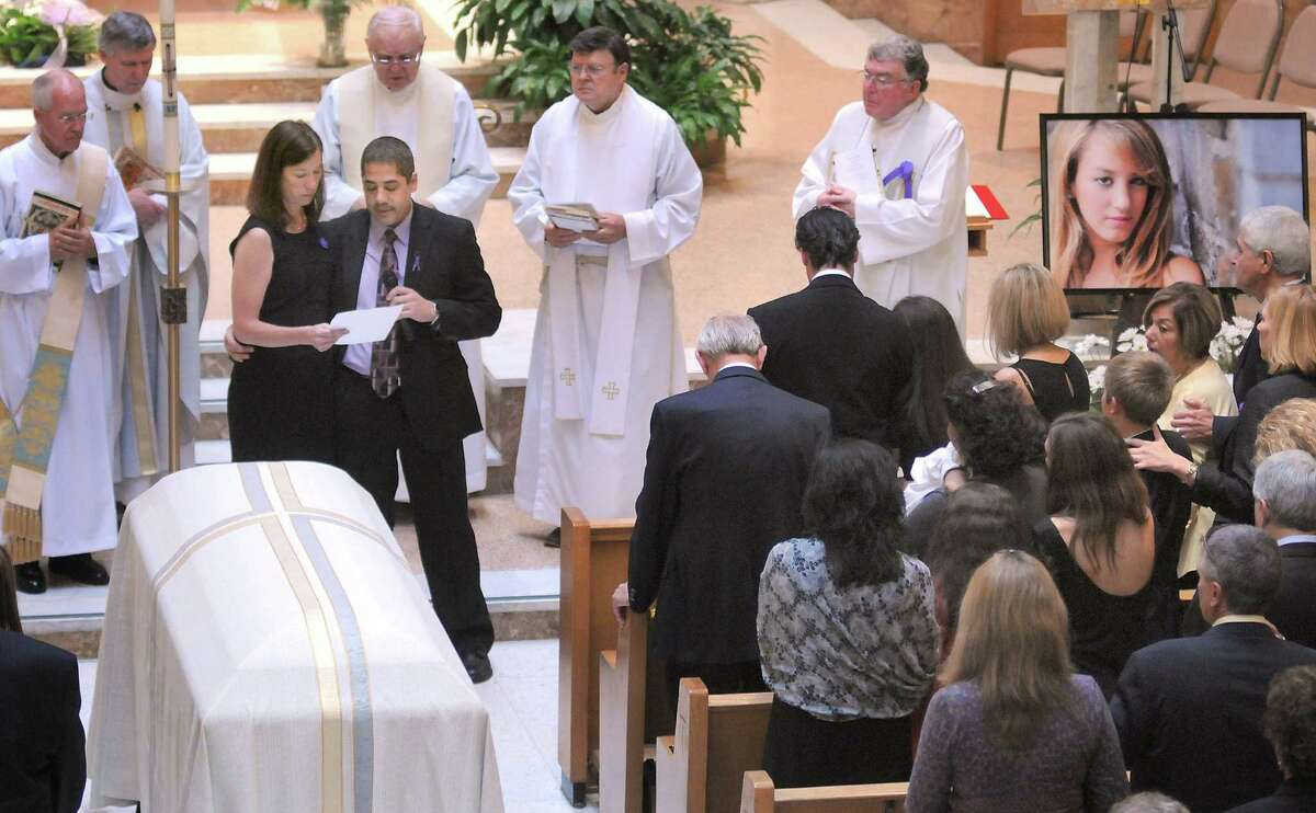 Kelly Kogut and Victor Gerace, third from left, the godmother and godfather of Alexandra Kogut, read a statement at her funeral service at St. John the Evangelist Church, Thursday, Oct. 4, 2012, in New Hartford, N.Y. Kogut's body was found early Saturday in her dorm room at the State University of New York College at Brockport, near Rochester. Her boyfriend Clayton Whittemore, of New Hartford, is charged with the killing. (AP Photo/Observer-Dispatch, Mark DiOrio, Pool)