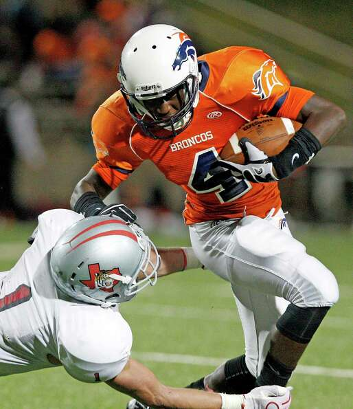 Bush's Javonte McGill #4 breaks the tackle of Fort Bend Travis' Cody Moncure.