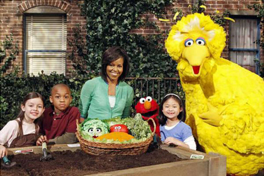 Current First Lady Michelle Obama poses with Big Bird.  (Richard Termine / The Associated Press)
