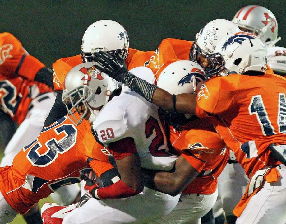 Ikenna Amaliri #20 is group tackled by Bush's  defense. Photo: Thomas B. Shea, For The Chronicle / © 2012 Thomas B. Shea