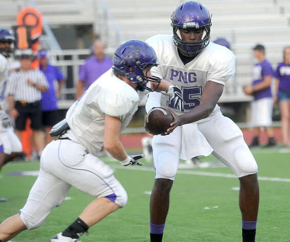 PN-G's A.J. Smith hands off to Spencer Wommack during the Purple/White Spring Football game at PN-G in Port Neches,  Friday, May 25, 2012. Tammy McKinley/The Enterprise Photo: TAMMY MCKINLEY