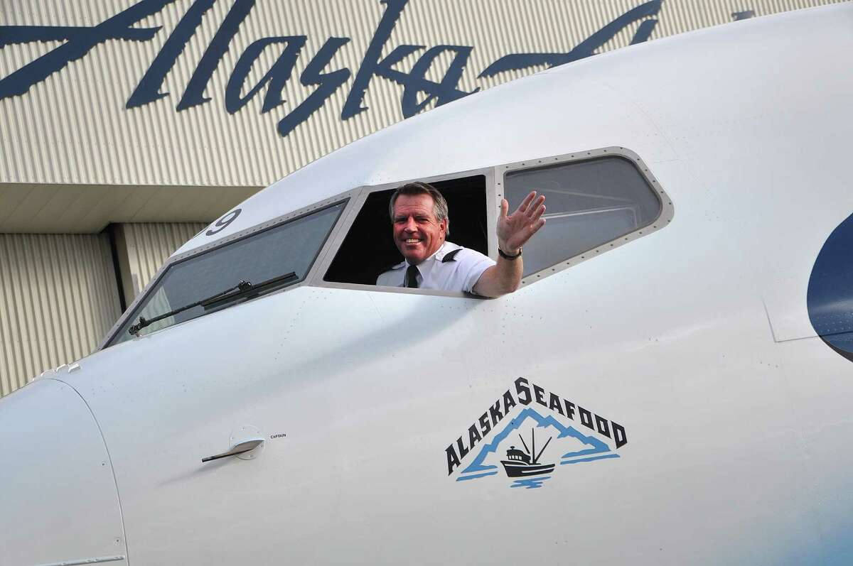 """An Alaska Airlines pilot waves from the flight deck of the carrier's new """"Salmon-Thirty-Salmon II,"""" a Boeing 737-800. The airplane celebrates Alaska Airlines' partnership with the Alaska Seafood Marketing Institute."""