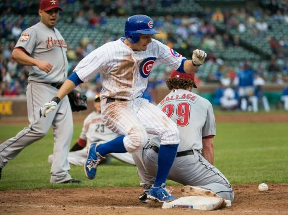 Cubs outfielder Tony Campana is safe at first base with a bunt single as the throw from Astros second baseman Tyler Greene gets past first baseman Brett Wallace during the ninth inning. (Smiley N. Pool / Houston Chronicle)