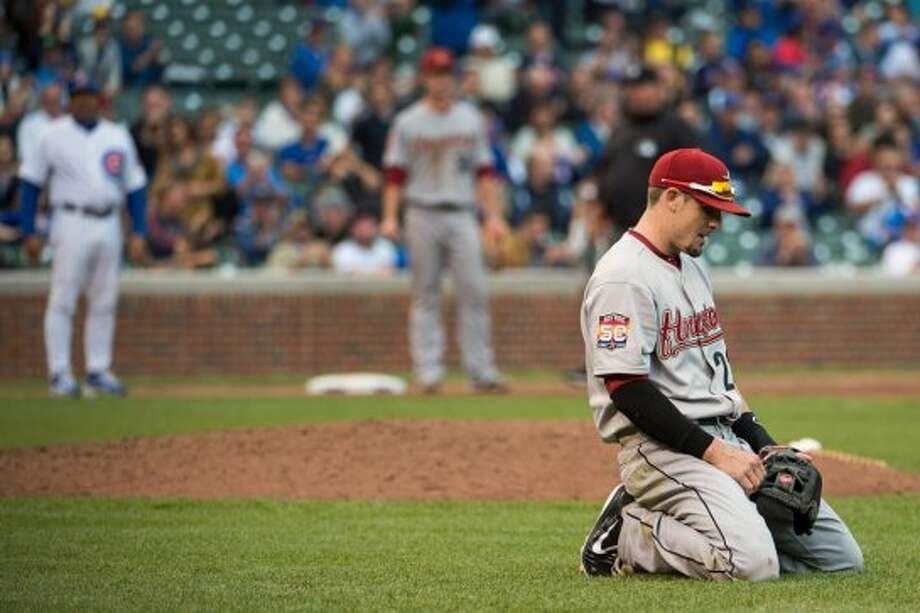 Astros second baseman Tyler Greene kneels on the infield after failing to throw out Tony Campana of the Cubs on a bunt single during the ninth inning. (Smiley N. Pool / Houston Chronicle)