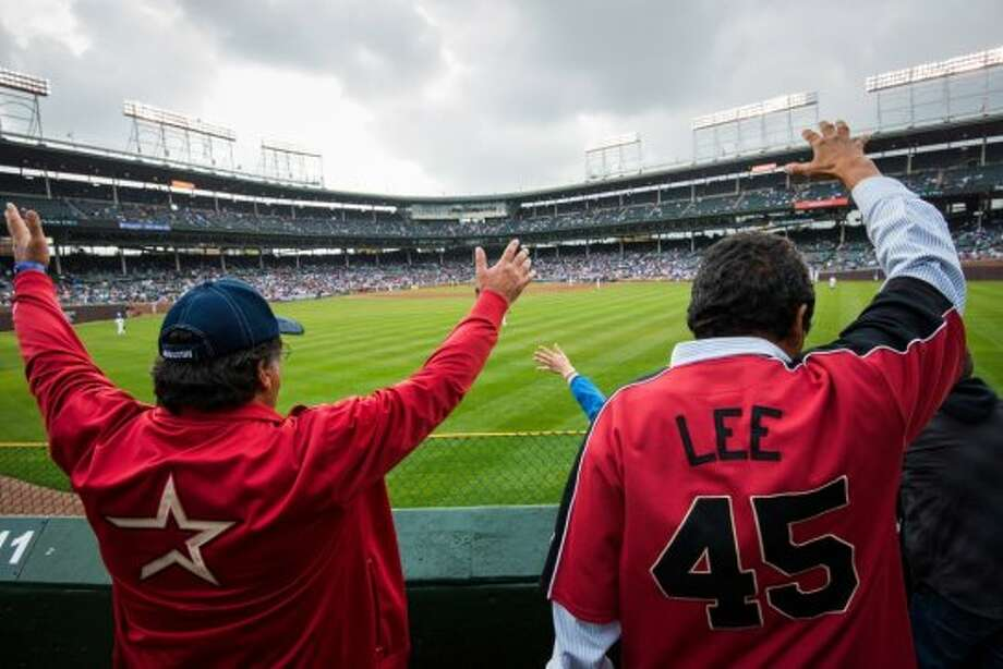 Astros fans Jerry Acevedo, left, and Robert Fong, both from Houston, yell for a ball from Chicago Cubs center fielder Brett Jackson during the sixth inning at Wrigley Field. Acevedo and Fong made the one-day trip to Chicago for the game. (Smiley N. Pool / Houston Chronicle)