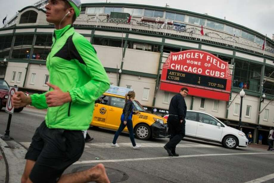 Pedestrians, including a barefoot man running, pass the Wrigley Field marquee showing the Chicago Cubs leading the Houston Astros 4-1 in the fourth inning. (Smiley N. Pool / Houston Chronicle)