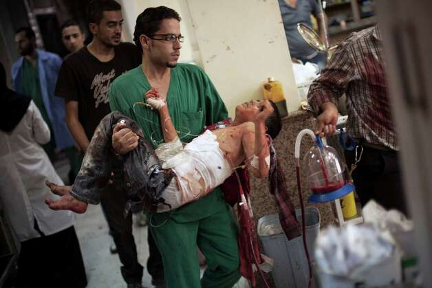 A doctor carries a severely wounded Syrian boy in the Dar El Shifa hospital, in Aleppo, Syria Thursday, Oct. 4, 2012 after the child was hit by Syrian Army shelling. The border violence between Turkey and Syria has added a dangerous new dimension to Syria's civil war, dragging Syria's neighbors deeper into a conflict that activists say has already killed 30,000 people since an uprising against President Bashar Assad's regime began in March 2011. (AP Photo/ Manu Brabo) Photo: Manu Brabo