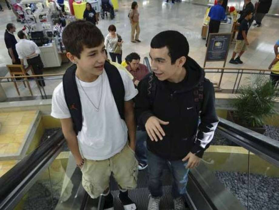 Austin Mahone, left, and his friend, Robert Villanueva, ride an escalator at North Star Mall on Saturday, Nov. 19, 2011. BILLY CALZADA / gcalzada@express-news.net (BILLY CALZADA / SAN ANTONIO EXPRESS-NEWS)