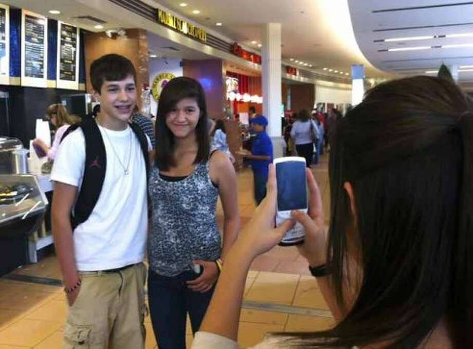 Austin Mahone, 15, who has dreams of becoming a big star, poses for a picture with fan Dominique Villarreal, as her friend, Taylor Barrios, snaps a picture, at North Star Mall on Saturday, Nov. 19, 2011. The girls recognized Mahone from his presence on the internet. (AP Photo/Billy Calzada, San Antonio Express-News) (Billy Calzada / Associated Press)