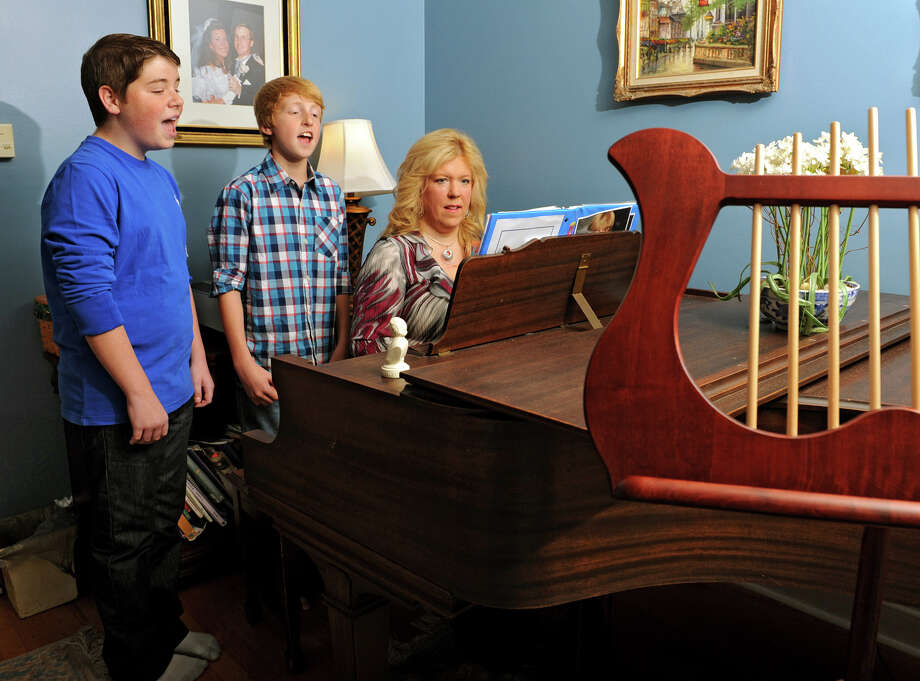 Voice instructor Lisa Franklin plays the piano as her son George, 12, middle, and Jack Mastrianni, 13, of Slingerlands sing a show tune at Franklin's home Wednesday, Sept. 26, 2012 in Loudonville, N.Y. The boys won parts in the Broadway production of A Christmas Story. (Lori Van Buren / Times Union) Photo: Lori Van Buren