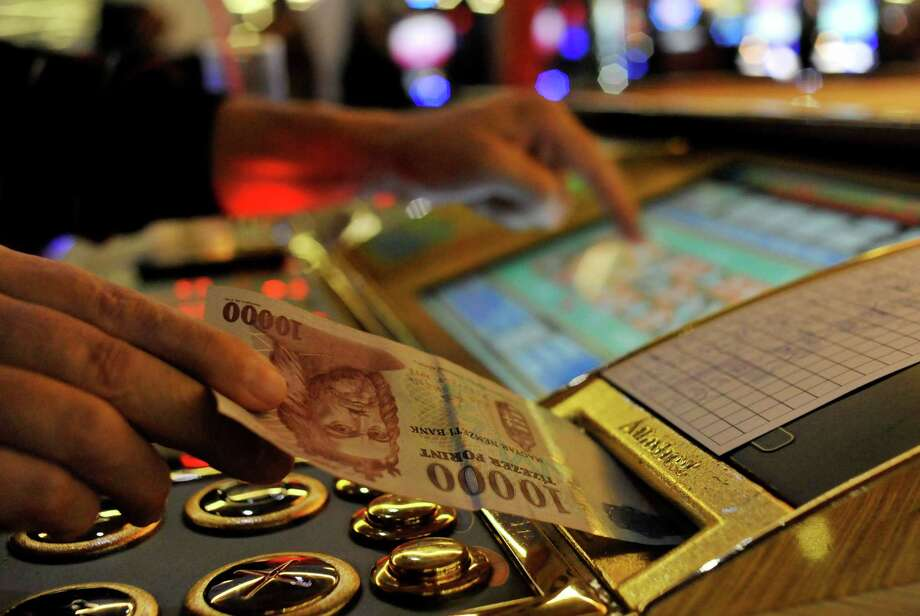 A man inserts a bill into a slot machine roulette in a gambling hall in Budapest, Hungary, Wednesday, Oct. 3, 2012. Hungary's ban on slot machines has taken the country's gambling industry by surprise. On Tuesday, just over 24 hours after the announcement, lawmakers in the Hungarian Parliament voted in favor of a new bill which bans the country's slot machines. (AP Photo/Bela Szandelszky) Photo: Bela Szandelszky