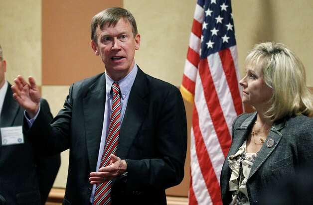 Colorado Gov. John Hickenlooper, left, gestures as he answers a question at a news conference in Oklahoma City, Thursday, Oct. 4, 2012. Looking on at right is Oklahoma Gov. Mary Fallin. Fallin and Hickenlooper are leading a group of 22 states that want to use compressed natural gas vehicles in their fleets. (AP Photo/Sue Ogrocki) Photo: Sue Ogrocki, STF / AP
